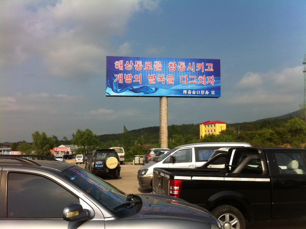 A billboard ad by Hunchun City, facing Korea, exhorting pushing forward together to open transportation routes.
