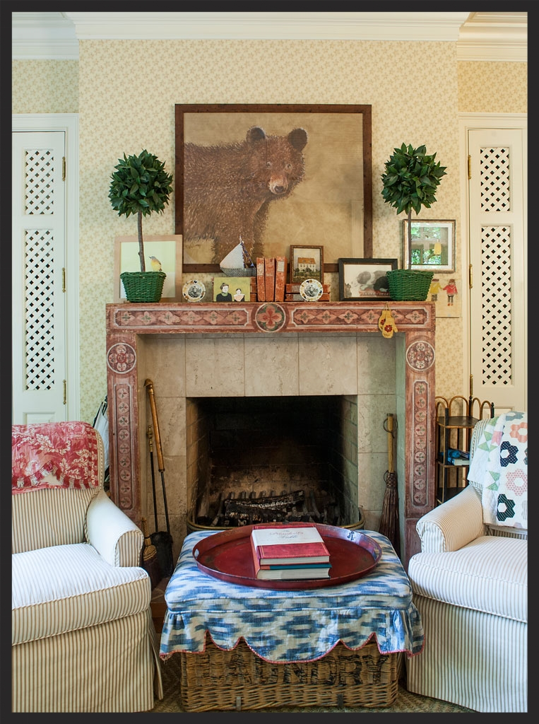Various objects on painted mantle.   Old wicker laundry basket with French fabric used as ottoman.  Linda Kay McCloy - alittleenglishinteriors.com