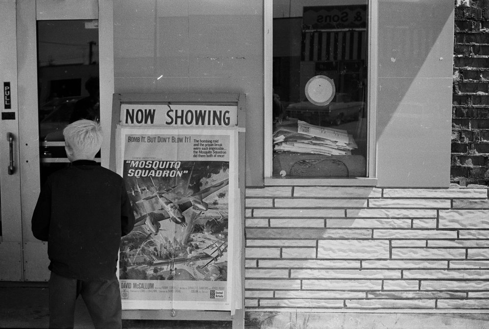 A Boy Looking at Theatre Posters