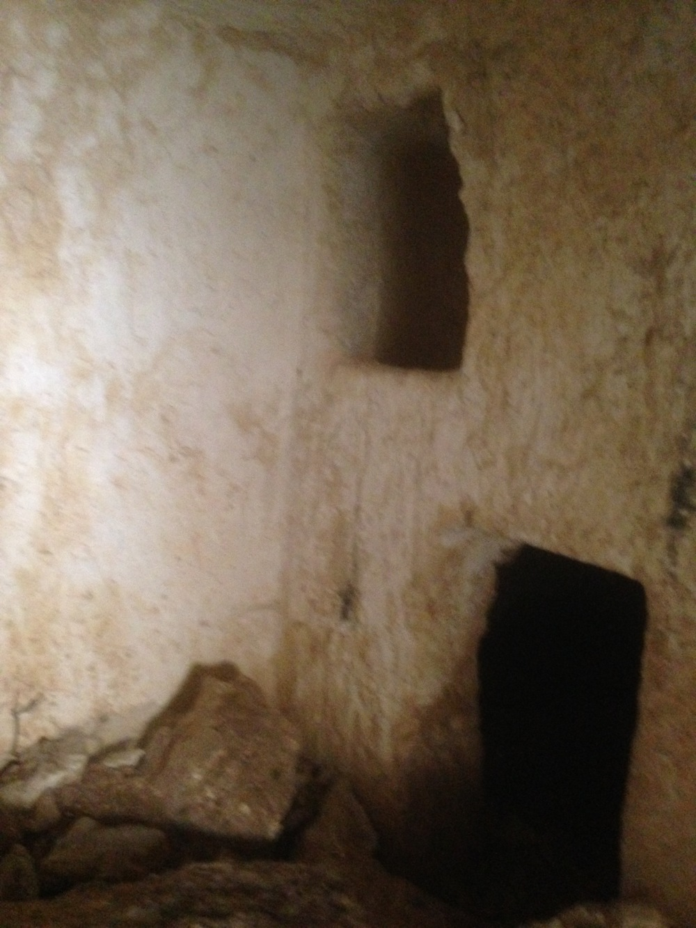 The hole above is where a body would be placed. The hole below is where ossuaries would be stacked. So the grave could be used for several members of the family.