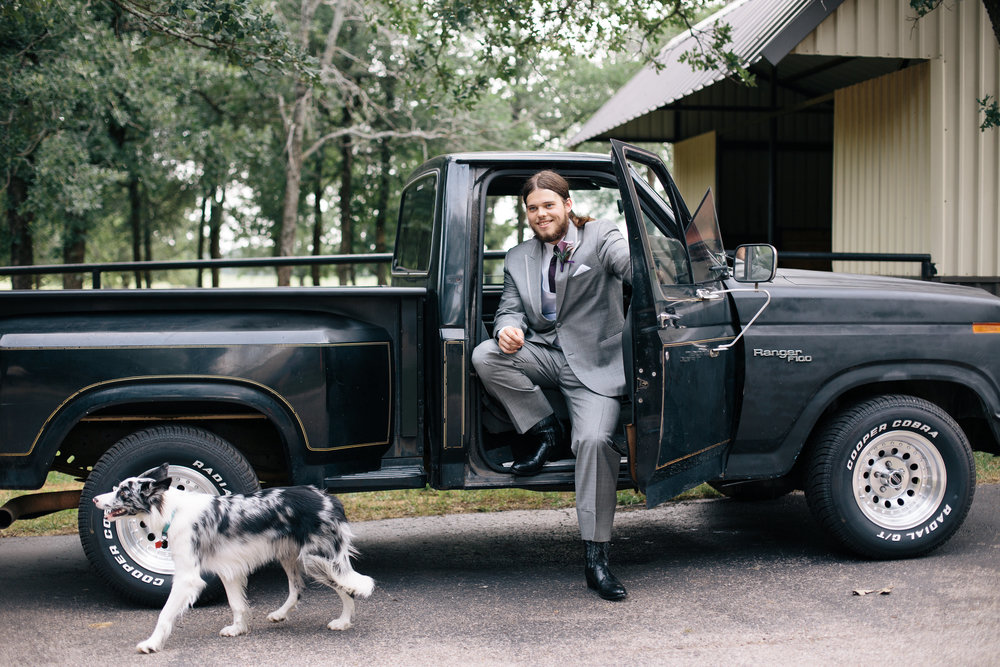 Groom in old truck at Classic Oaks Ranch with dog