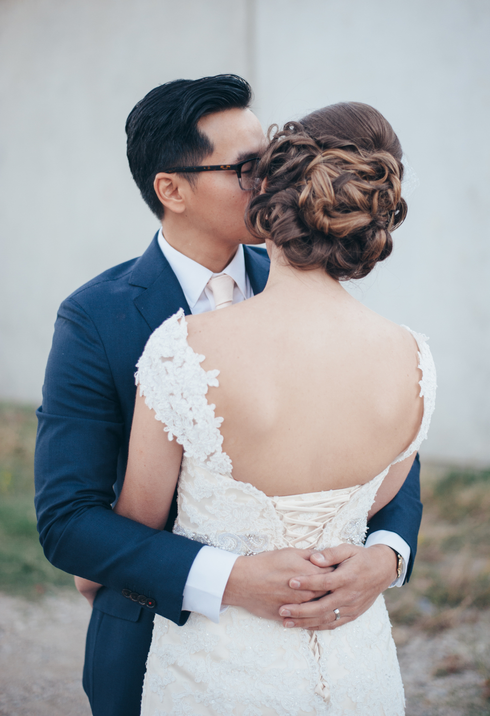 Groom kissing bride; updo