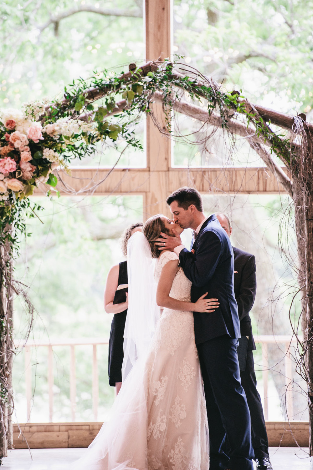 Bride & Groom Kiss Under Arch