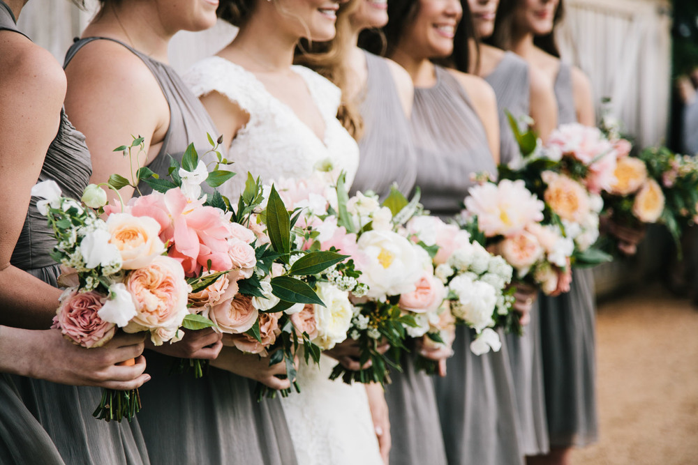 Gray bridesmaid dresses; peach and white flowers