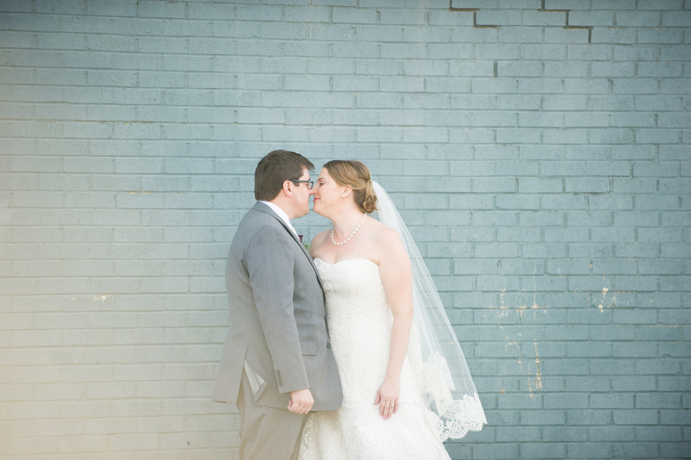Bride & groom kissing blue wall