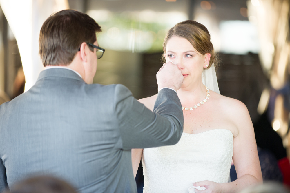 Wedding ceremony groom blotting tears