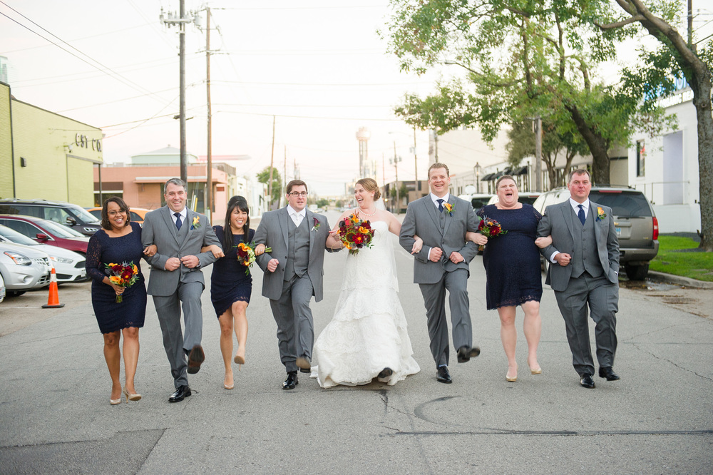 Bridal party walking in Dallas gray suits navy bridesmaids