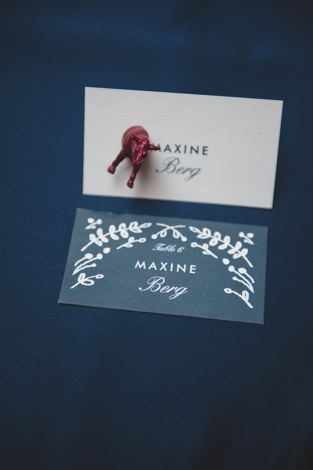 Navy leaf escort card with animal magnet favor