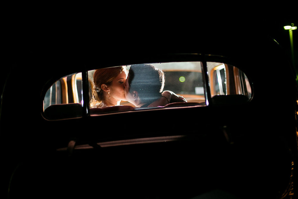 Bride & groom kissing in getaway car