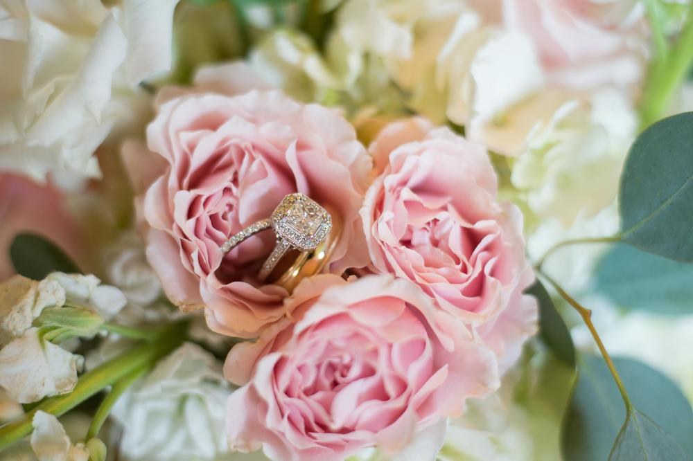 Engagement ring & wedding band on pink flowers