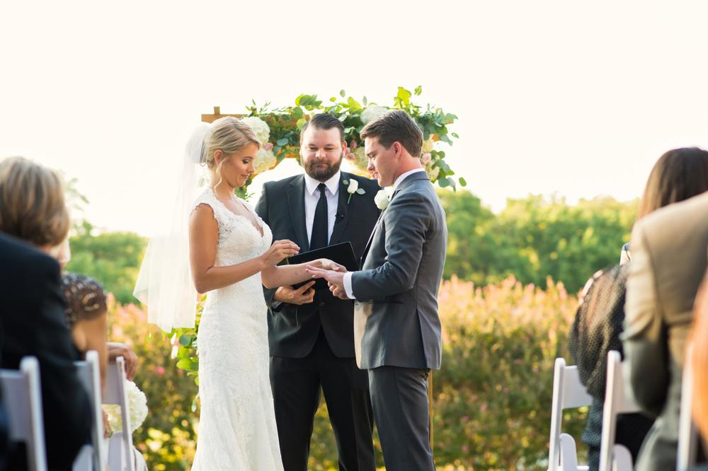 Outdoor wedding ceremony exchanging rings