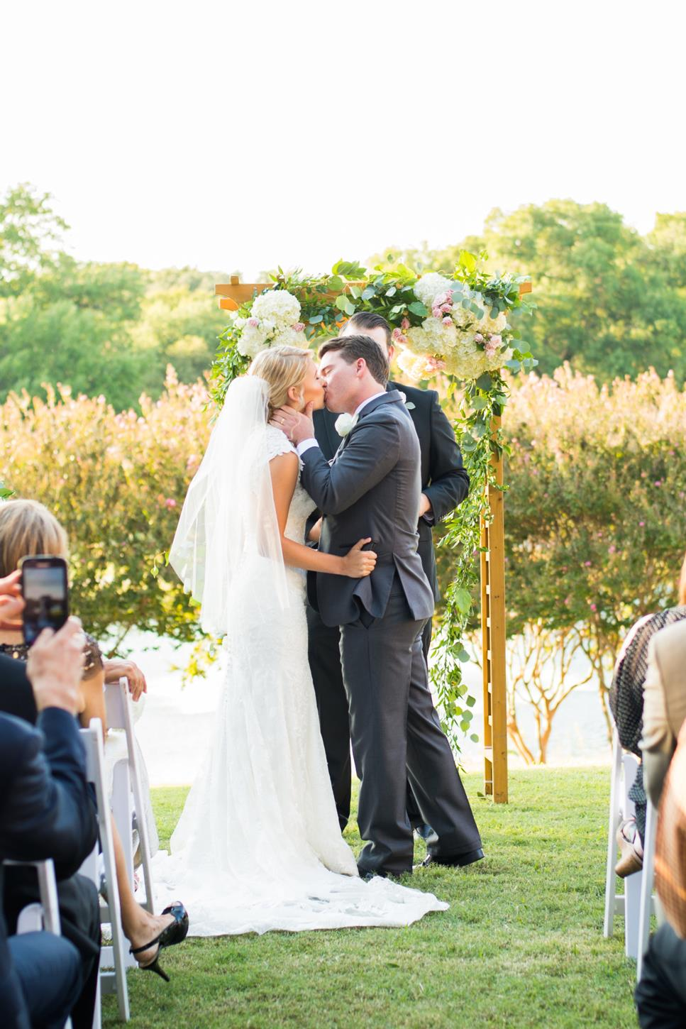 Outdoor wedding ceremony kiss