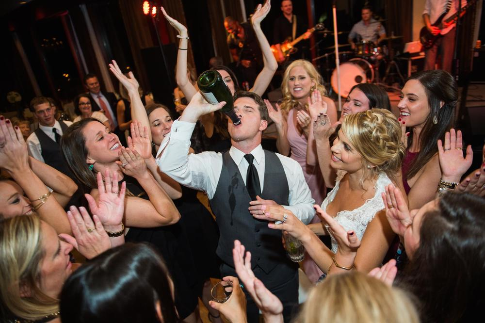 Groom chugging champagne on dance floor