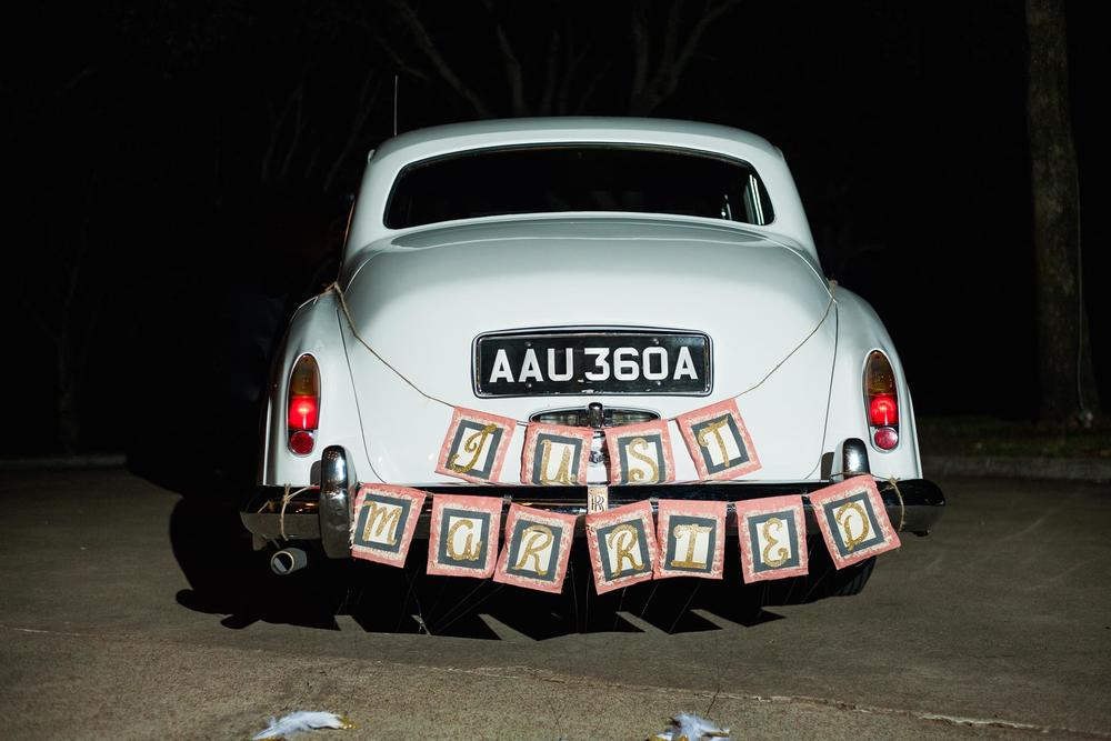 "Classic white wedding getaway car with ""just married"" banner"