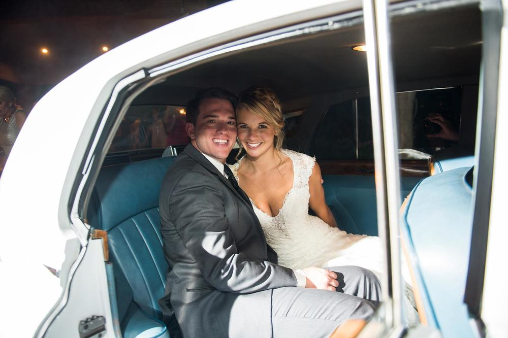 Bride & groom in getaway car