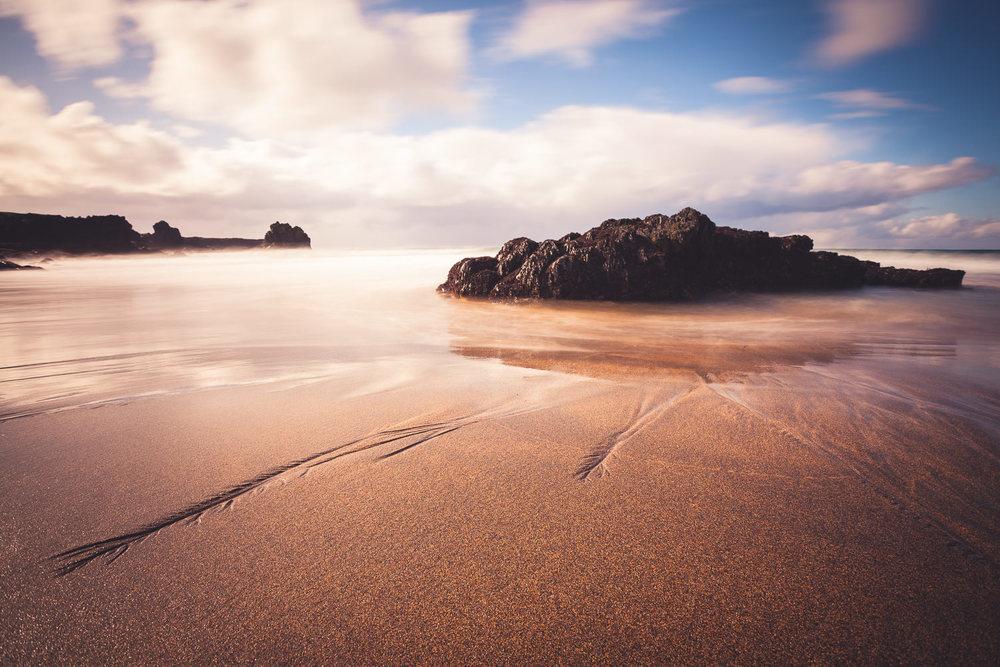 A golden beach nestled in between dark, basaltic cliffs.
