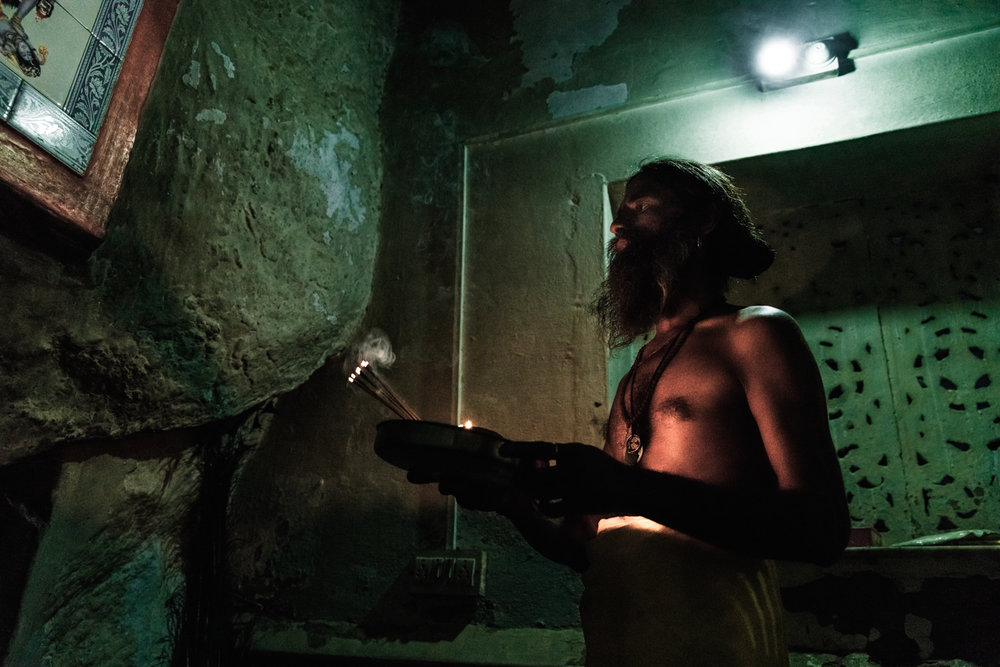 A Sadhu named Mohandas making an offering at his temple cave.