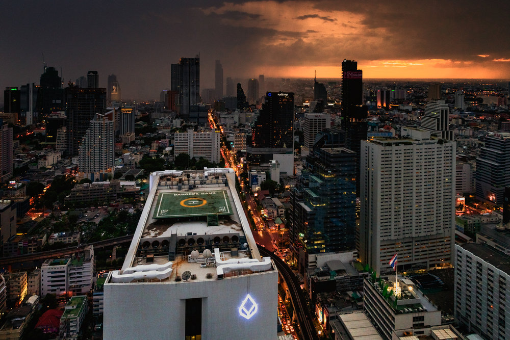 A storm sweeps through downtown Bangkok at sunset.