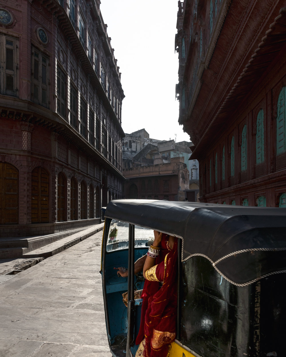Women ride in a tuktuk through the streets of Bikaneer.