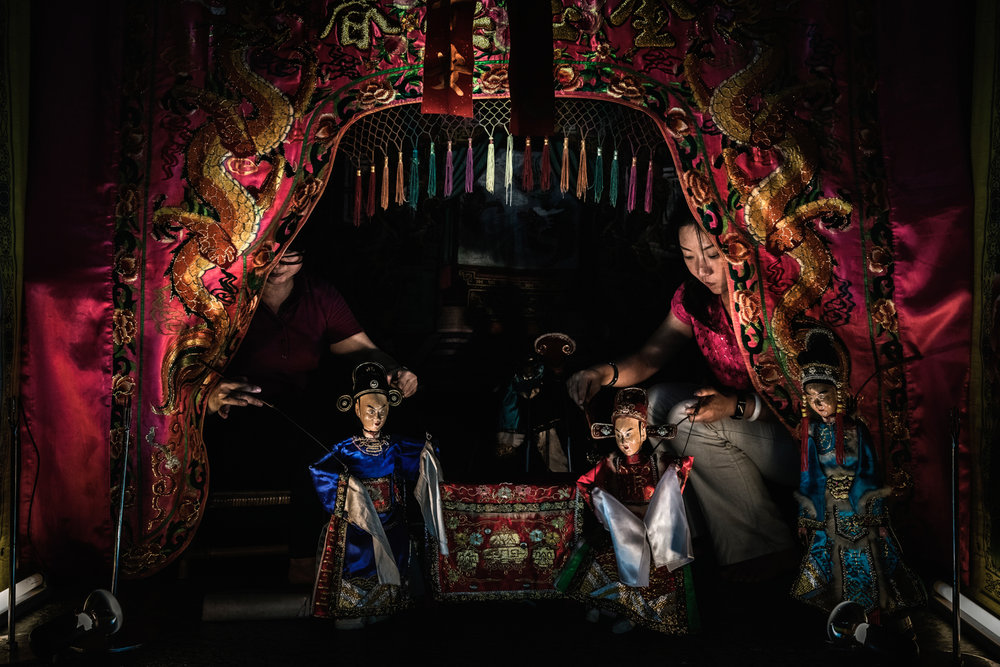 Two women perform a traditional Hokkien puppet show during the Hungry Ghost Festival.