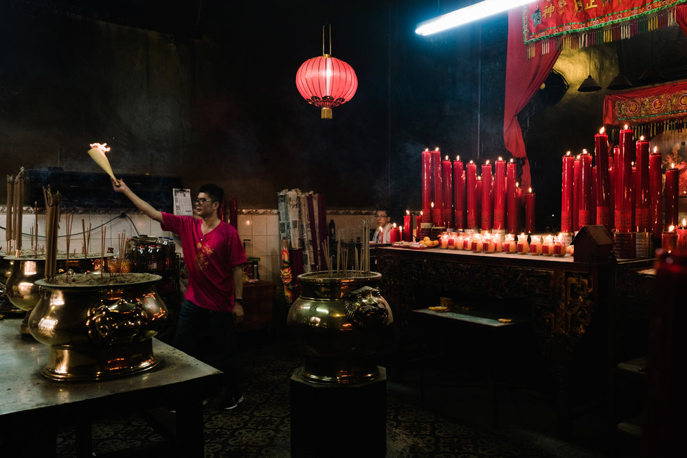 A man carries joss sticks as an offering in a Taoist temple.