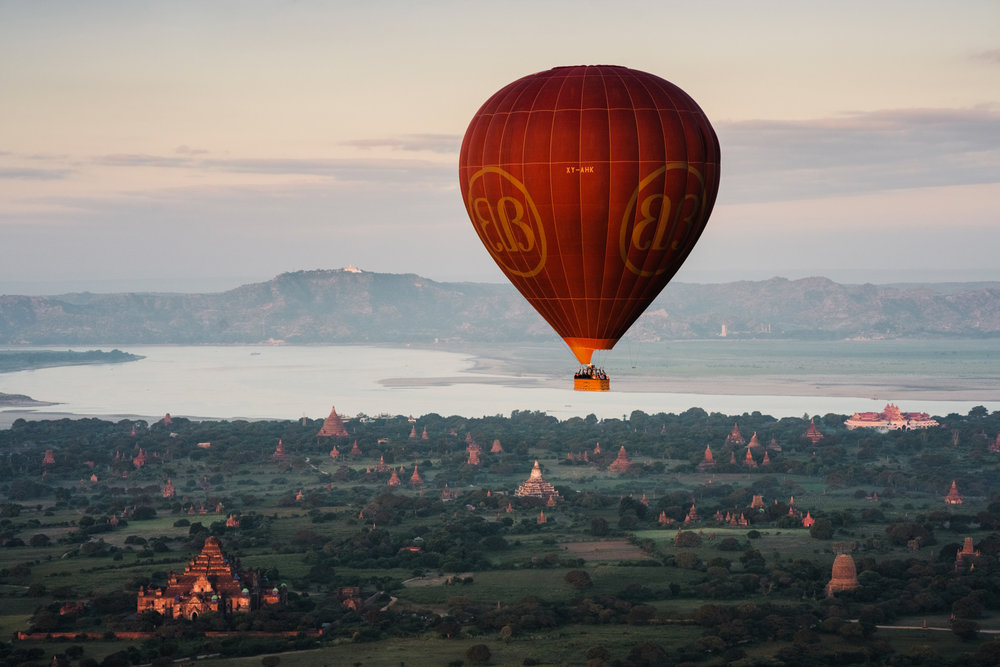 A hot air balloon above the plains of Bagan where thousands of ancient temples sit.
