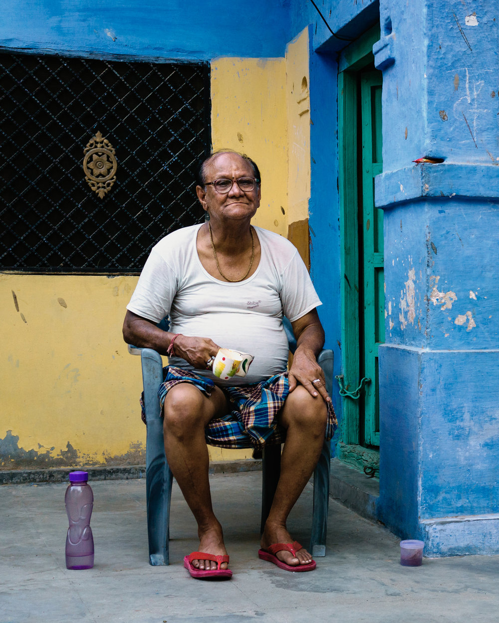 A elderly man drinks tea outside of his house in the Blue City.