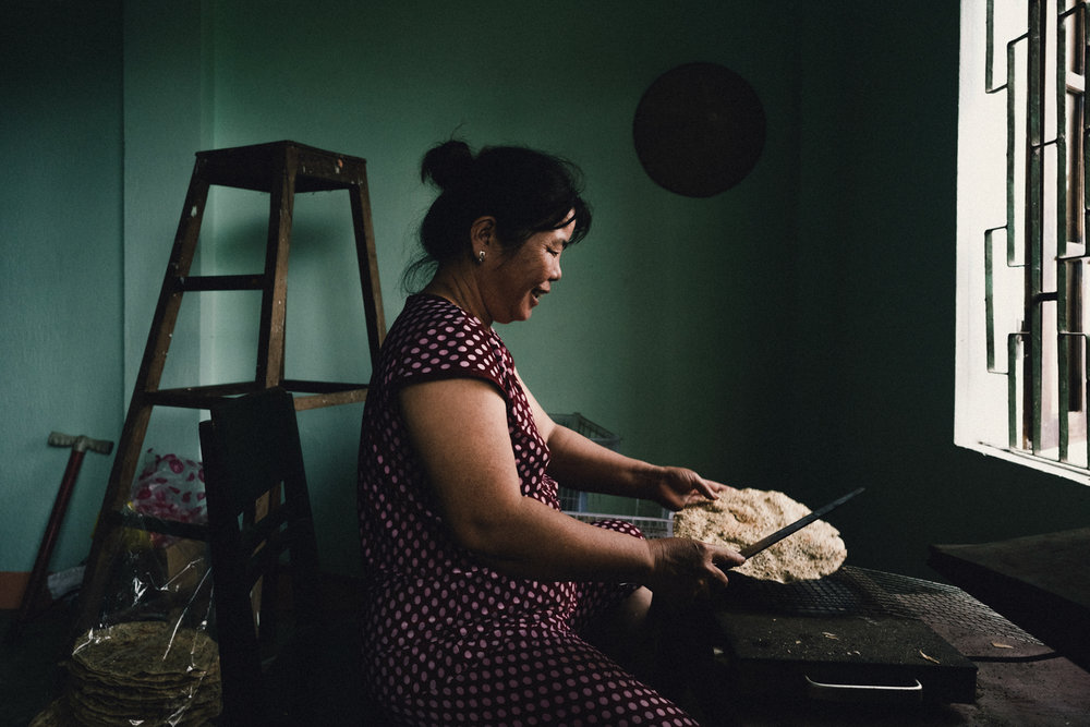A women making rice crackers in her house.