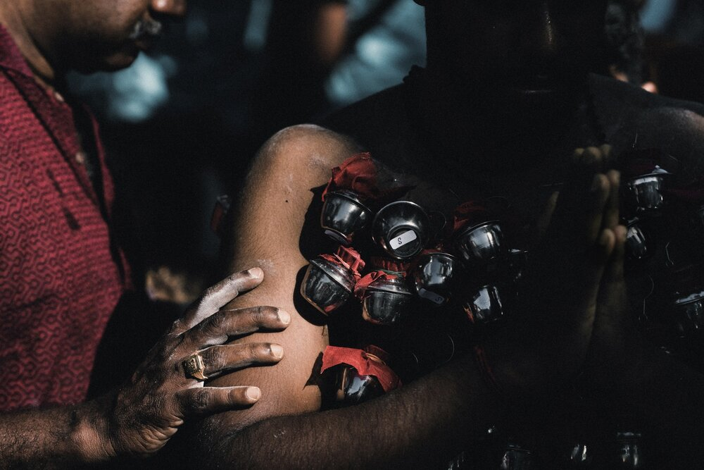 A man comforts a younger devotee during the body modification ritual during the Thaipusam Festival.