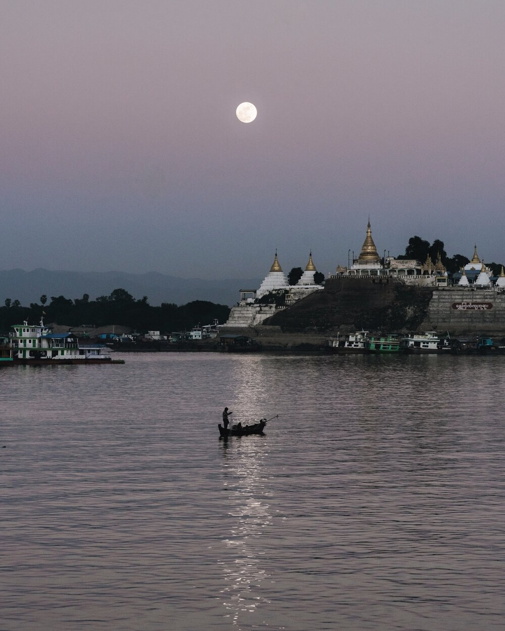 A full moon rises on the Irrawaddy River.