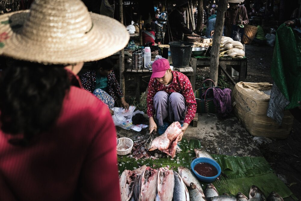 A women buying fish at a Inle Market.
