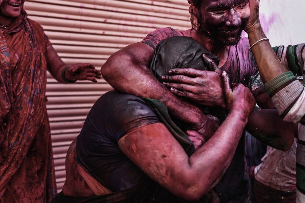 A family cover each other in colourful dyes during Holi Festival.