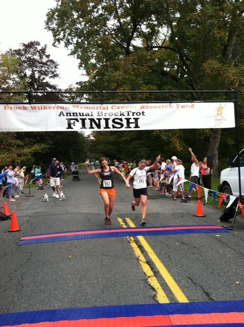 Caroline crossing the finish line with big sis Lizzie