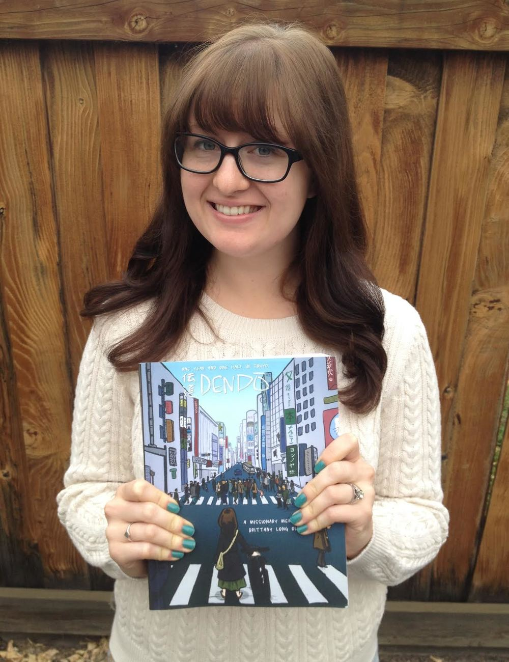 Brittany holding a copy of the graphic novel she self-published about her volunteer experiences in Japan.