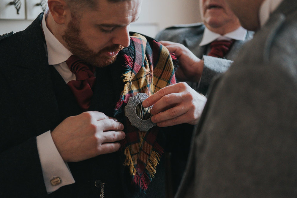 the groom getting ready for his wedding with best man and father. wearing a kilt