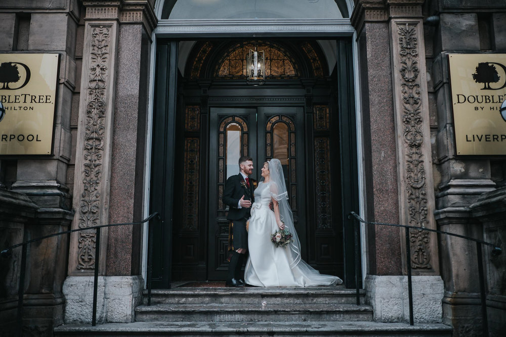 bride and groom on the steps at the front of the double tree by Hilton in Liverpool