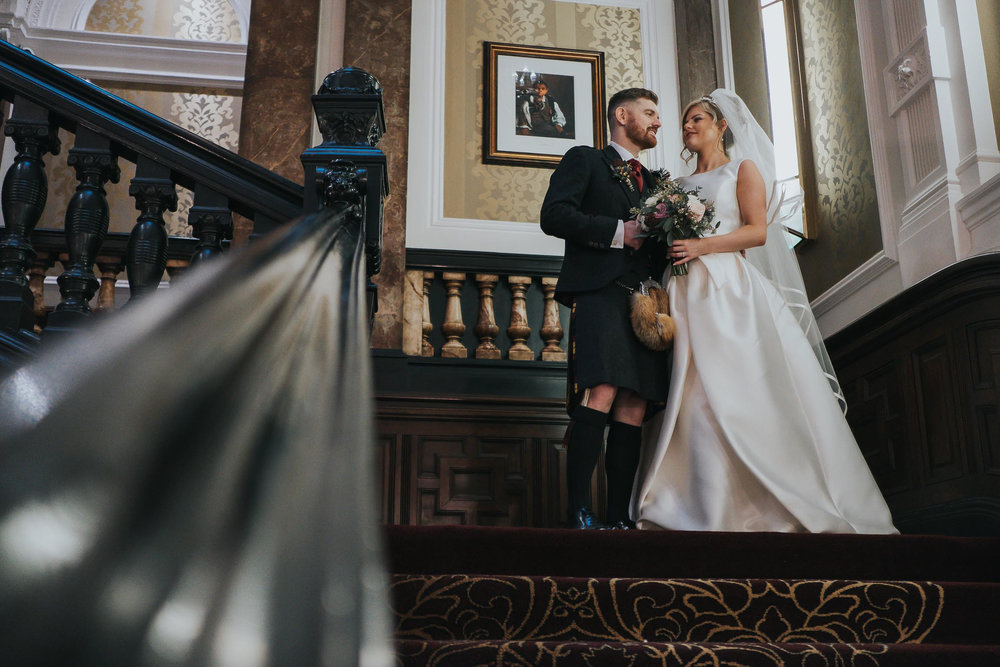 bride and groom stood on the staircase at the Double Tree in Liverpool