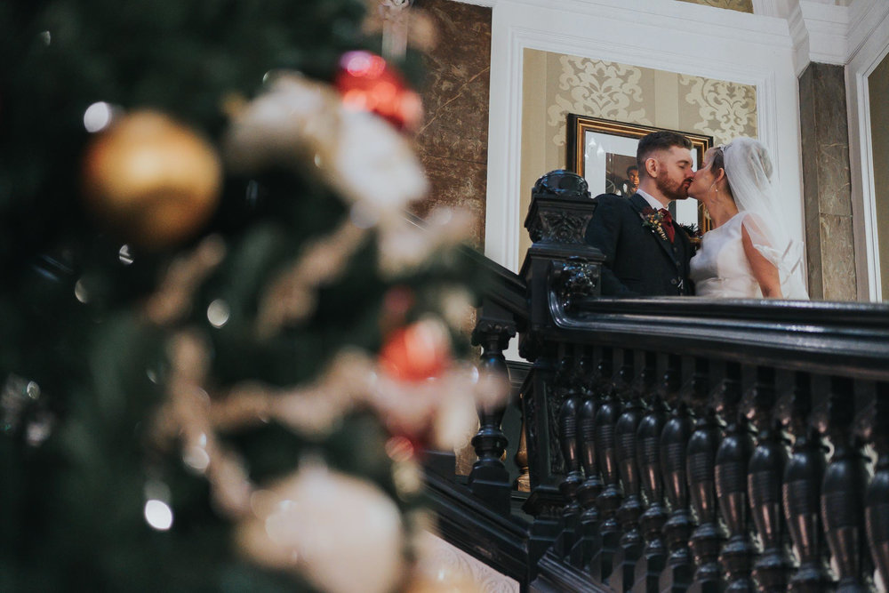 Bride and groom with Christmas tree in the foreground in Liverpool Hilton