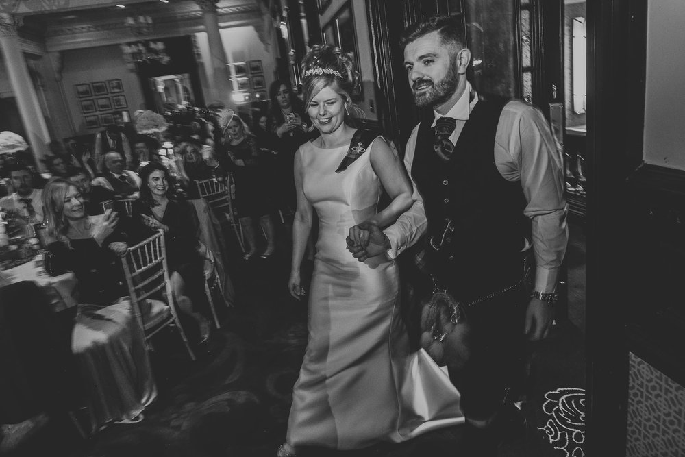 black and white image of a bride and groom being announced in to their wedding evening party