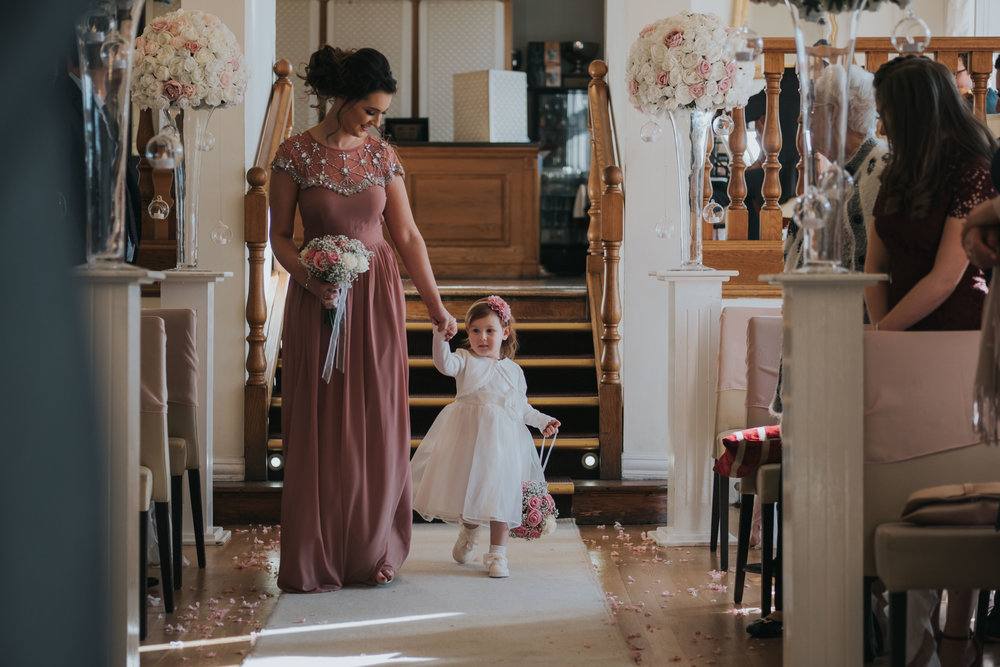 Bridesmaid and flower girl walking down the aisle on their wedding day at west tower exclusive wedding venue in ormskirk
