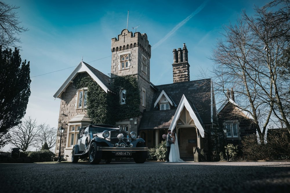 bride and groom outside west tower exclusive wedding venue in ormskirk on their wedding day stood next to the wedding car by church town cars