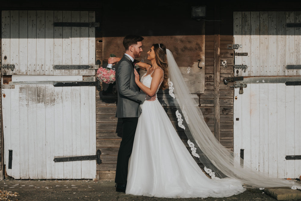 bride and groom outside stable doors after tying the know on their wedding day