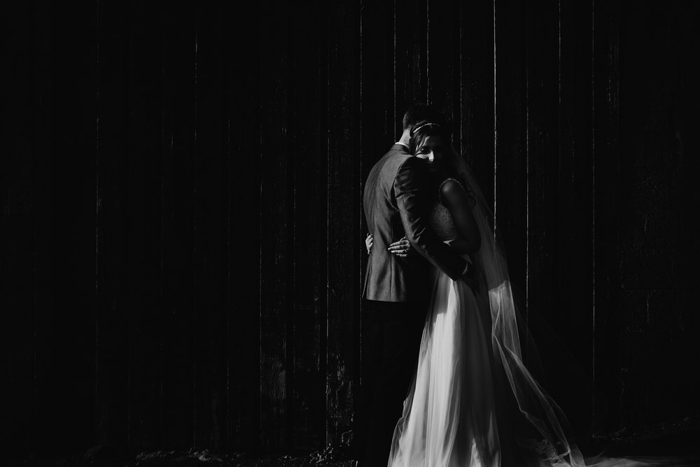black and white image of a bride and groom hugging after becoming man and wife