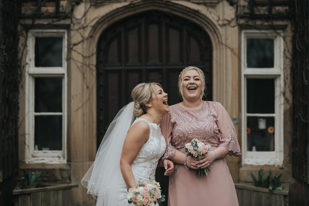 two sisters bride and bridesmaid enjoying some fun on the wedding day