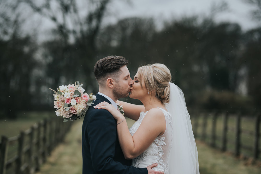 kissing in the rain on their wedding day  at The Villa in Wrea Green