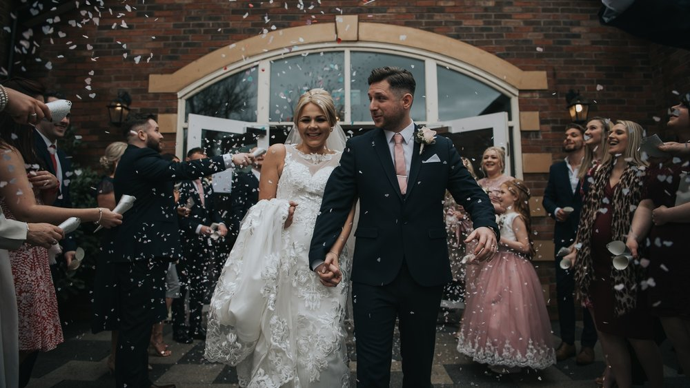 Bride and groom celebrating their wedding day with confetti at The Villa in Wrea Green
