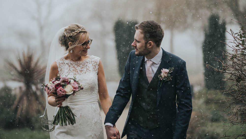 The happy couple walking in the snow at the Grosvenor Pulford during their wedding day