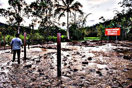 Hombre mira el terreno donde solía estar su casa, ahora destruida e inundado por el río Tundayme.