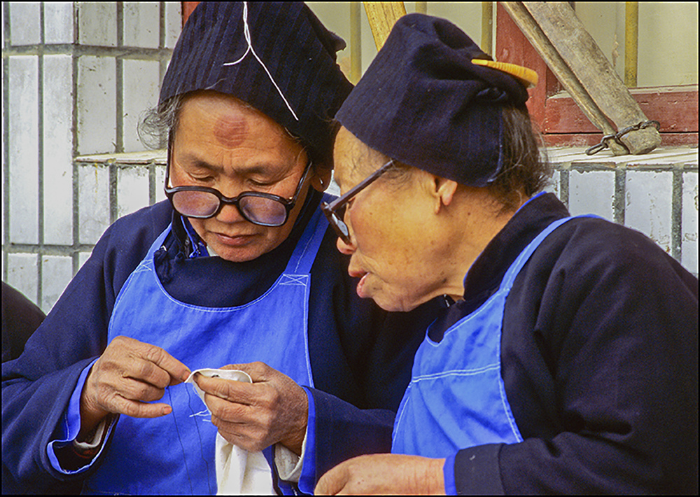 Comparing stitches, Guizhou, China