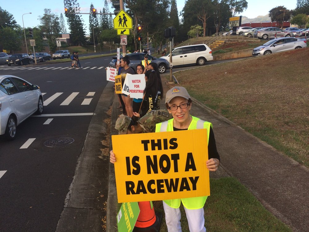 Holding signs on Meheula Parkway to discourage speeding